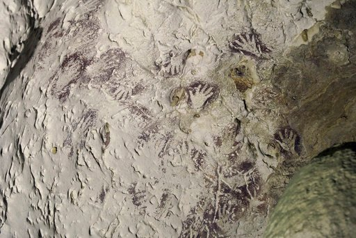 (Kinez Riza via AP). This undated photo provided by Kinez Riza shows mulberry-colored hand stencils in a cave in the Indonesian part of the island of Borneo. This particular style of hand stencil dates to the height of the Last Glacial Maximum about 20...