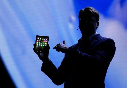 (AP Photo/Eric Risberg). Justin Denison, SVP of Mobile Product Development, shows off the Infinity Flex Display of a folding smartphone during the keynote address of the Samsung Developer Conference Wednesday, Nov. 7, 2018, in San Francisco.