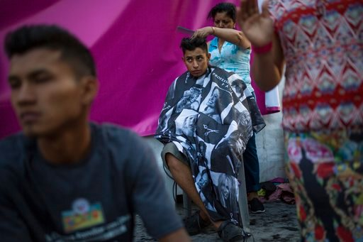(AP Photo/Rodrigo Abd). Honduran migrant Luis Fernando Barahona looks at an ongoing catholic mass while a hairdresser cuts his hair at a shelter at the Jesus Martinez stadium, in Mexico City, Wednesday, Nov. 7, 2018. Humanitarian aid converged around t...