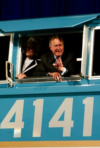 (AP Photo/Pat Sullivan, File). FILE - In this Oct. 18, 2005, file photo, former President George H.W. Bush and his wife Barbara wave out the window of a new locomotive numbered 4141 in honor of the 41st president at Texas A&M University in College ...