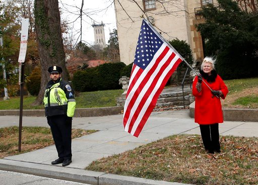 (AP Photo/Alex Brandon, Pool). People line the streets to pay their respects as the hearse with the casket of former President George H.W. Bush passes by from the Capitol on the way to a State Funeral at the National Cathedral, Wednesday, Dec. 5, 2018,...