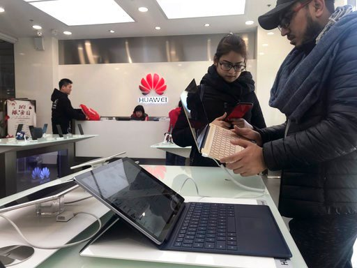 (AP Photo/Ng Han Guan). Foreigners look at a Huawei computer at a Huawei store in Beijing, China, Thursday, Dec. 6, 2018. Canadian authorities said Wednesday that they have arrested the chief financial officer of China's Huawei Technologies for possibl...