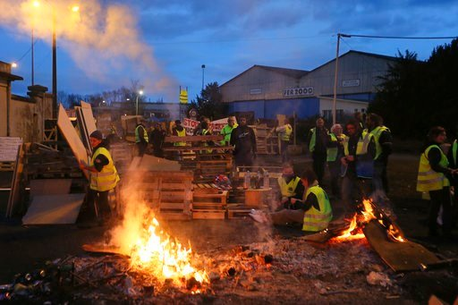 """(AP Photo/David Vincent). FILE - In this Tuesday, Dec. 5, 2018 file photo, demonstrators stand at a makeshift barricade set up by the """"yellow jackets"""" protesters to block the entrance of a fuel depot in Le Mans, western France. Even proponents of carbo..."""