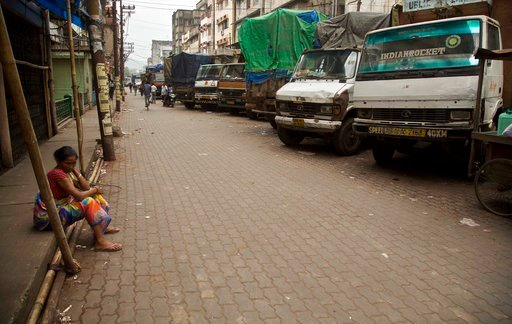 (AP Photo/Anupam Nath). FILE - In this Monday, Sept. 10, 2018 file photo, a laborer sits near trucks at a closed market during a day-long strike to protest rising fuel prices among other economy issues, in Gauhati, India. Even proponents of carbon taxe...