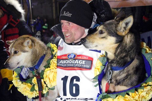 (AP Photo/Mark Thiessen, File). FILE - In this March 15, 2016, file photo, Dallas Seavey poses with his lead dogs Reef, left, and Tide after finishing the Iditarod Trail Sled Dog Race in Nome, Alaska. Iditarod officials have cleared a four-time champio...
