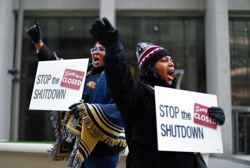(AP Photo/Paul Sancya). Cheryl Monroe, right, a Food and Drug Administration employee, and Bertrice Sanders, a Social Security Administration employee, rally to call for an end to the partial government shutdown in Detroit, Thursday, Jan. 10, 2019.