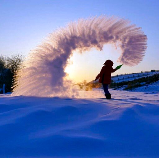 (Mikhail Tilpunov via AP). In this handout photo taken on Tuesday, Feb. 5, 2019, a woman throws boiling water into the freezing air as its instantly condenses into an elaborate pattern of ice crystals in Irkutsk, Russia . Residents of Russia's Urals an...